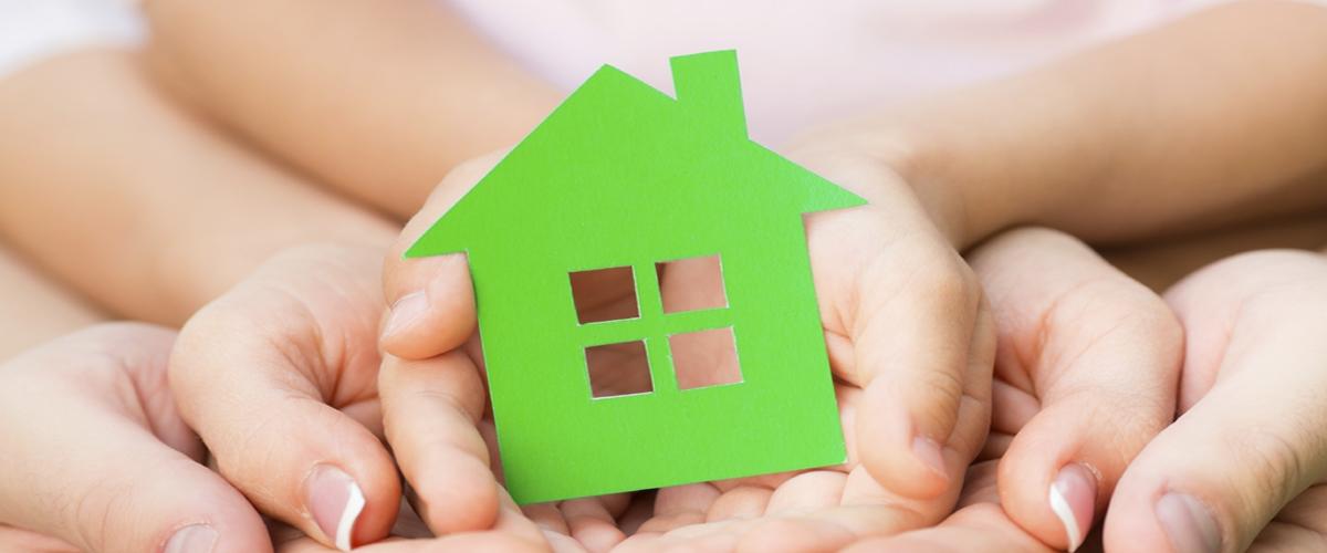 Immagine di alcune mani che tengono un piccola casa ecologica di cartone.